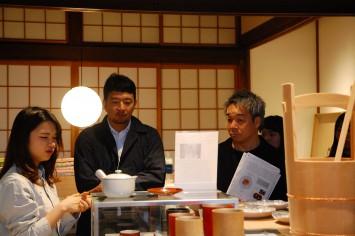 『D&DEPARTMENT KYOTO』店内で、京都造形芸術大学の学生による商品説明に耳を傾けるナガオカケンメイ氏