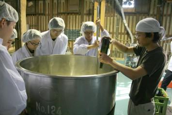 麹と水の入ったタンクに酵母菌を流し入れる。作業をする学生も、見学する学生も真剣そのものだ