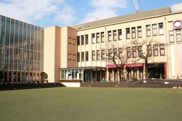 京都国際マンガミュージアムの外観。緑色のグランドとクリーム色の建物がオシャレ