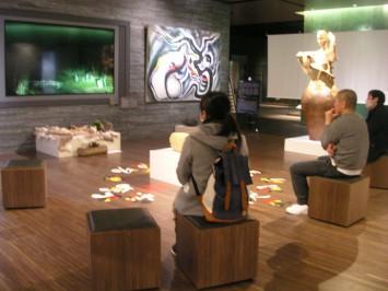 モニターには映像作家・井上亜美作「猟師の生活」「じいちゃんとわたしの共通言語」「まなざしをさす」が流れる。絵画は岡本太郎作「石と樹」、彫刻家・藤原彩人の磁釉陶が並ぶ (C)Ami Inoue (C)岡本太郎記念館 (C)藤原彩人