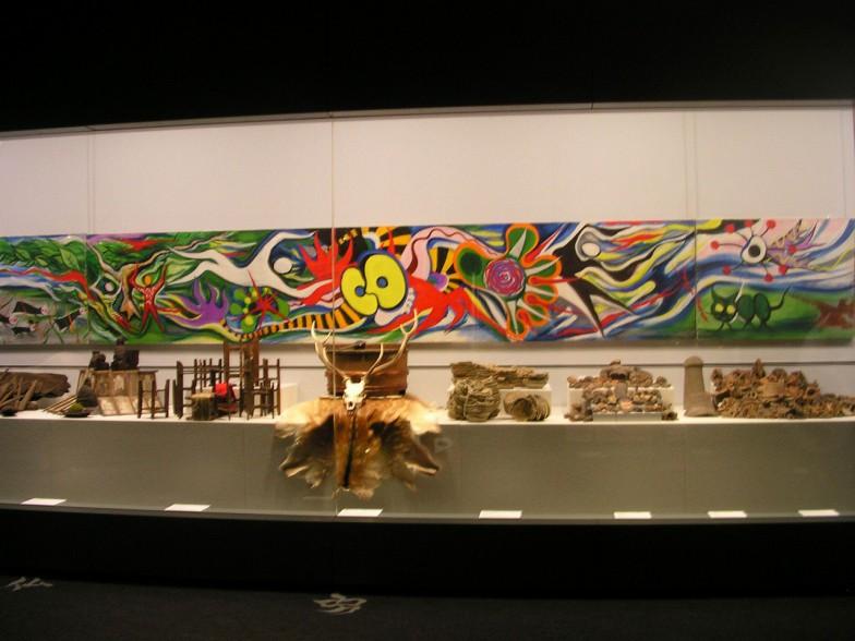 目にドーンと飛び込んでくる岡本太郎作「豊饒の神話」。作品を背景に縄文人に食べられた鹿の角や骨、縄文時代の土器と土偶、古墳時代の武具、近代の民具が並ぶ2.5次元「豊饒の間」。 (C)岡本太郎記念館