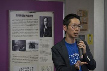 由来について話す橋本先生。うしろに写っている写真が濱崎先生による絵の元になったもの