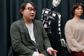 アンドロイド観音誕生の経緯について話す小川先生。研究室にはさまざまなアンドロイドたちもいる
