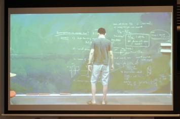 巨大な黒板に向き合う橋本教授の映像が投影された