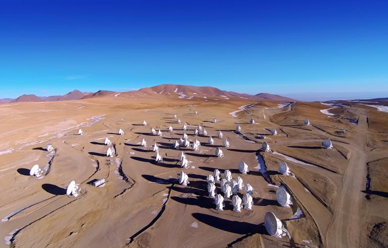 今回の観測で活躍した、チリのアタカマ砂漠に広がるアルマ望遠鏡。可動式の66台のパラボラアンテナがひとつの巨大な電波望遠鏡として機能している。Credit: ALMA (ESO/NAOJ/NRAO), A. Marinkovic/X-Cam