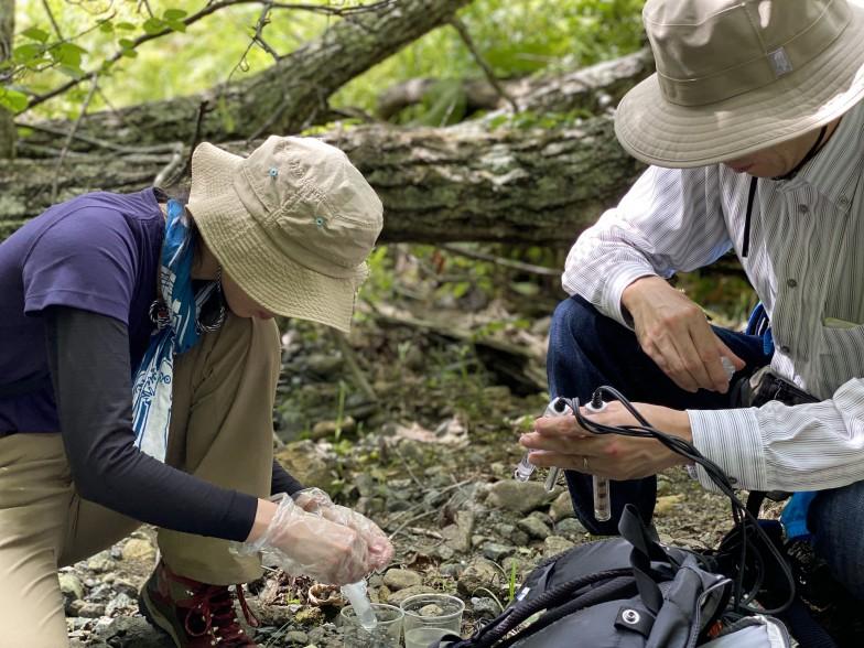 調査対象は多岐にわたる。こちらはヒグマに注意しながら北海道日高地域の廃鉱山周辺の河川を調査する様子。現地でpHや電気伝導度などを測定し、さらに詳しい化学分析を研究室で行うため、河川水や河床堆積物を採取して持ち帰る。