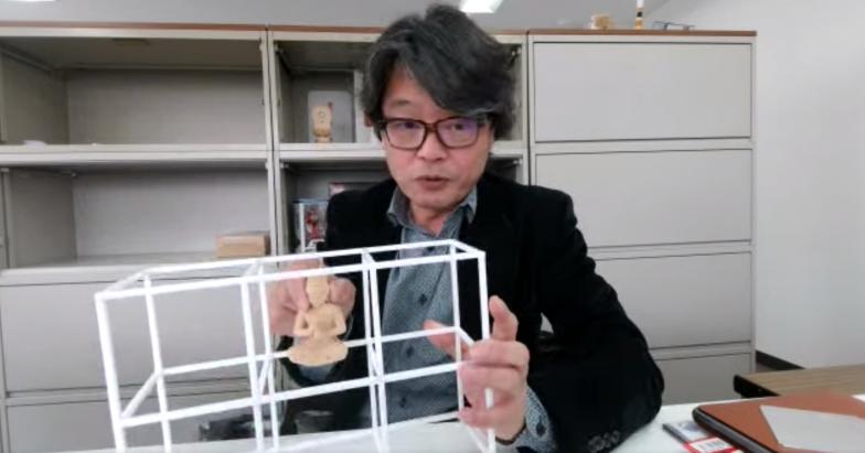 人工衛星と同じサイズのフレームを手に説明する北川さん。右手に持っているのは、ご本尊となる大日如来像のレプリカ