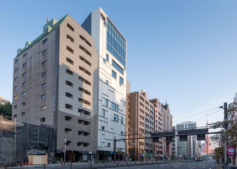 桜田通り沿いにある白い11階建のビルが東別館、外壁には慶應義塾のシンボルであるペンマークのモチーフが浮き出している。