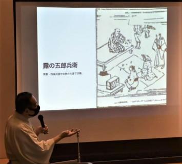 スライドに写っているのは落語家の祖の一人、露の五郎兵衛という人物。京都の北野天満宮の境内などで活躍しました。